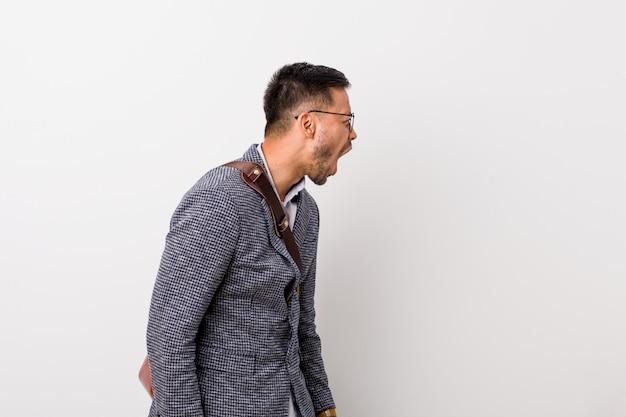 Jonge bedrijfs filippijnse mens tegen een witte muur die naar een exemplaarruimte schreeuwt Premium Foto