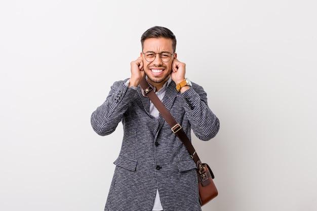 Jonge bedrijfs filippijnse mens tegen een witte muur die oren behandelen met handen. Premium Foto