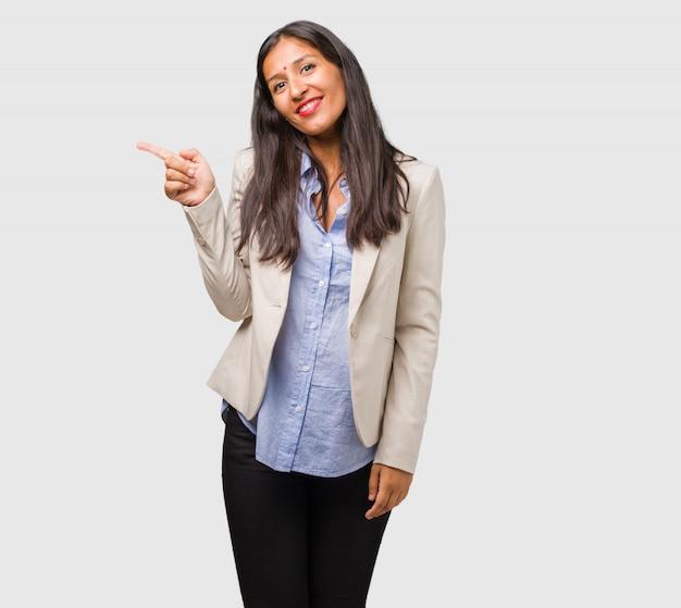 Jonge bedrijfs indische vrouw die aan de kant richt, verrast glimlachen voorstellend iets, natuurlijk en toevallig Premium Foto