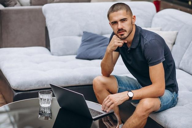 Jonge bedrijfsmens die aan een computer thuis werkt Gratis Foto