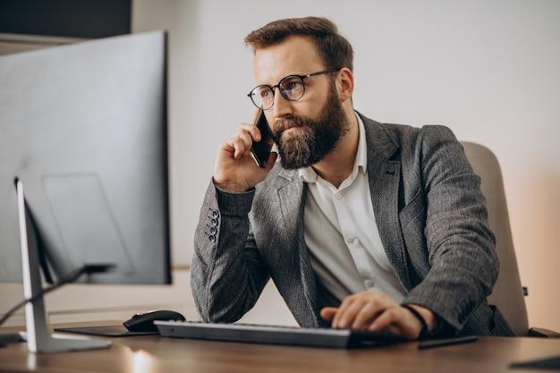 Jonge bedrijfsmens die over telefoon spreekt en aan computer werkt Gratis Foto