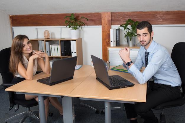 Jonge bedrijfsmens die samen met zijn collega werkt Premium Foto
