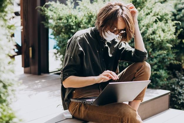 Jonge bedrijfsvrouw die aan computer van huis in masker werkt Gratis Foto