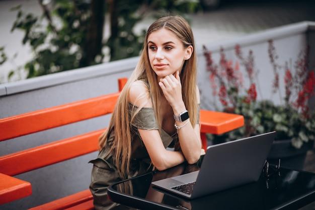 Jonge bedrijfsvrouw die aan laptop buiten in een koffie werkt Gratis Foto
