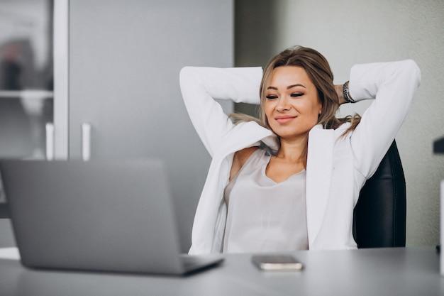 Jonge bedrijfsvrouw die aan laptop in een bureau werkt Gratis Foto