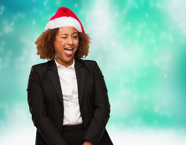 Jonge bedrijfsvrouw die een hoed van de chirstmassanta dragen funnny en vriendschappelijke tonende tong Premium Foto