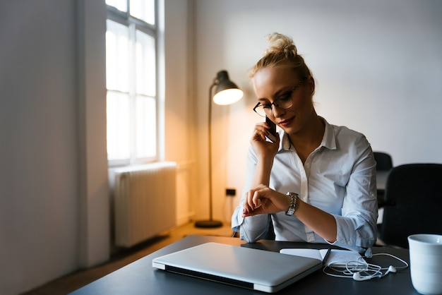 Jonge bedrijfsvrouw die op de telefoon in haar bureau spreekt Premium Foto
