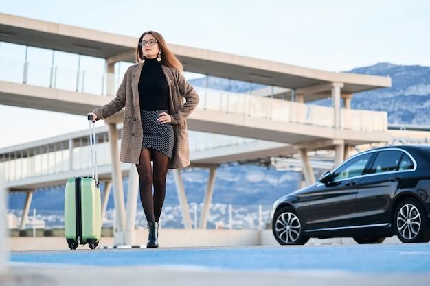 Jonge bedrijfsvrouw die tegen zwarte luxeauto loopt Premium Foto