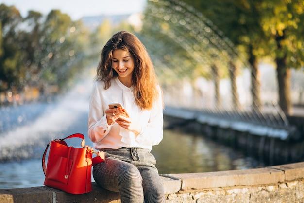 Jonge bedrijfsvrouw die telefoon in park met behulp van tijdens lunchtijd Gratis Foto