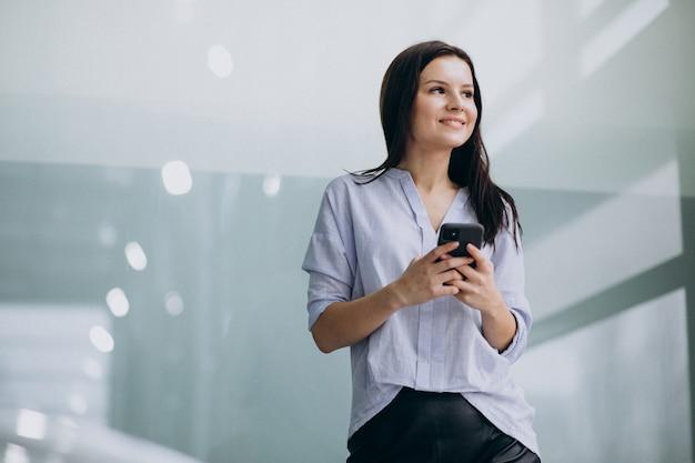 Jonge bedrijfsvrouw die telefoon met behulp van op het kantoor Gratis Foto
