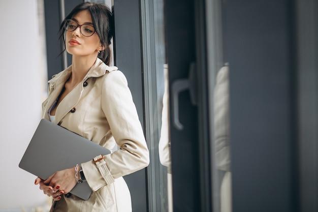 Jonge bedrijfsvrouw met laptop die zich door het venster in bureau bevindt Gratis Foto