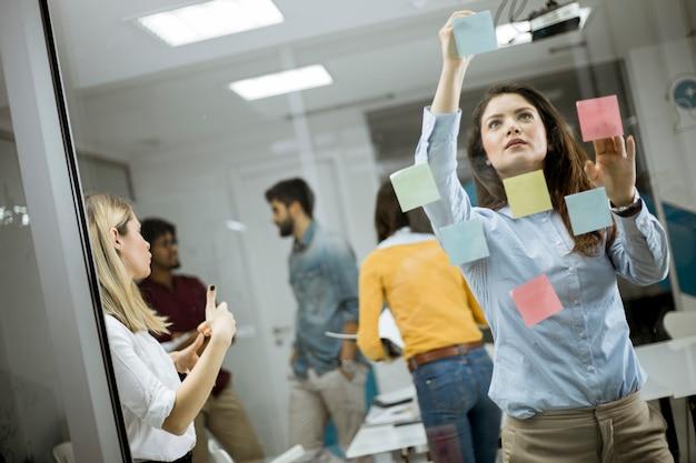 Jonge bedrijfsvrouwen die voor glasmuur bespreken die post-itnota's en stickers gebruiken Premium Foto