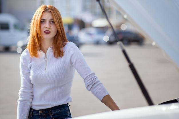 Jonge beklemtoonde vrouwenbestuurder die zich dichtbij broked auto met open kap bevinden. Premium Foto