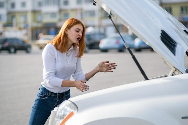 Jonge beklemtoonde vrouwenbestuurder die zich dichtbij broked auto met open kap bevindt. Premium Foto