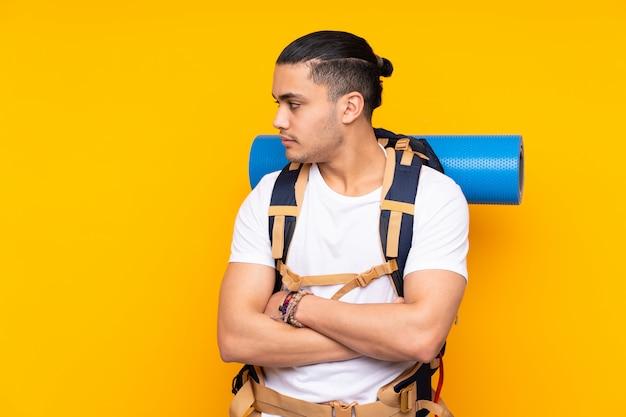 Jonge bergbeklimmer aziatische mens die met een grote rugzak op gele muur kant kijken Premium Foto