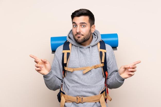 Jonge bergbeklimmermens met een grote rugzak over geïsoleerde muur die naar de zijtakken wijzen die twijfels hebben Premium Foto