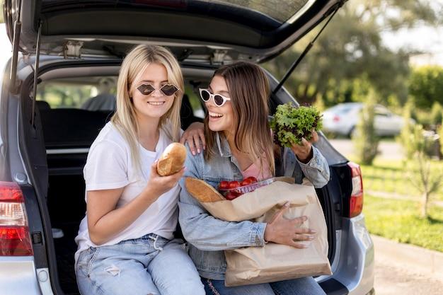 Jonge beste vrienden die in de kofferbak van een auto hangen Gratis Foto