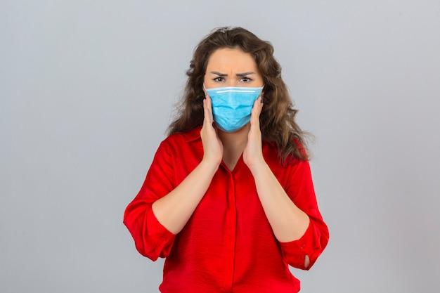 Jonge bezorgde vrouw die rode blouse in medisch beschermend masker draagt ?? wat betreft wangen die aan kiespijn lijden over geïsoleerde witte achtergrond Gratis Foto