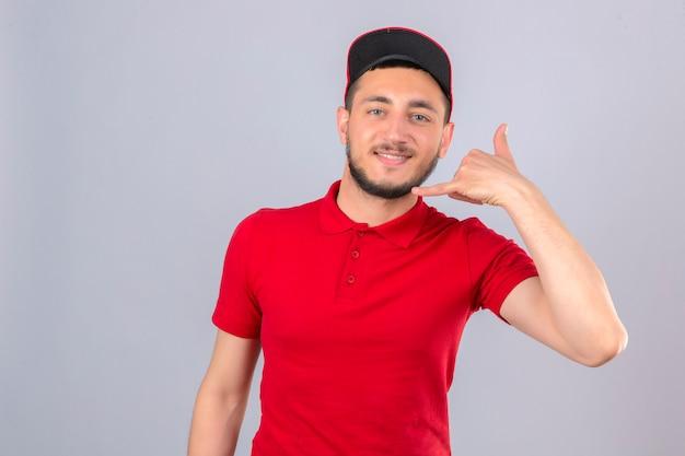 Jonge bezorger die een rood poloshirt en een pet draagt en bel me gebaar maakt op zoek naar zelfverzekerd over geïsoleerde witte achtergrond Gratis Foto