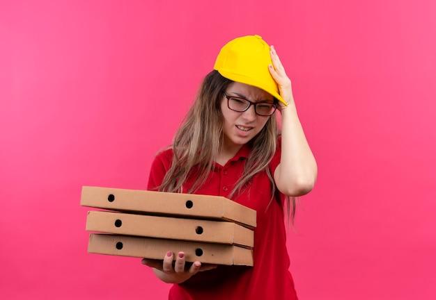 Jonge bezorger in rood poloshirt en gele pet met stapel pizzadozen die er verward en erg angstig uitzien met de hand op het hoofd voor een fout Gratis Foto