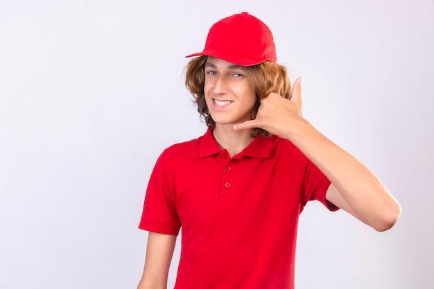 Jonge bezorger in rood uniform bel me gebaar op zoek zelfverzekerd glimlachend vrolijk over geïsoleerde witte achtergrond Gratis Foto