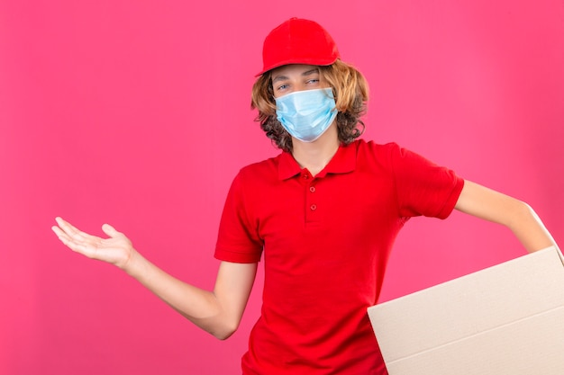 Jonge bezorger in rood uniform draagt ?? medisch masker met kartonnen doos glimlachend vrolijk presenteren en wijst met handpalm kijkend naar de camera over geïsoleerde roze achtergrond Gratis Foto