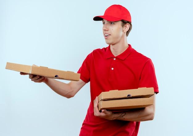 Jonge bezorger in rood uniform en pet die pizzadoos geeft aan een klant met een glimlach op het gezicht dat zich over een witte muur bevindt Gratis Foto