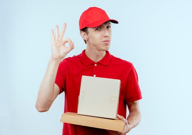 Jonge bezorger in rood uniform en pet met doos pakket en pizzadoos op zoek naar de voorkant glimlachend tonend ok teken staande over witte muur Gratis Foto