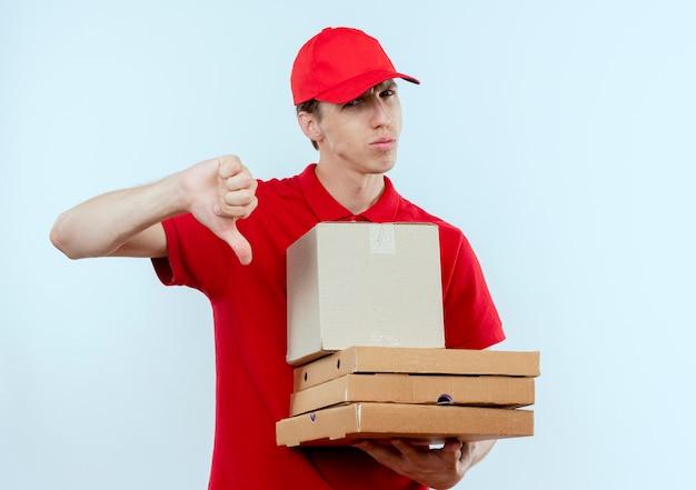 Jonge bezorger in rood uniform en pet met doos pakket en pizzadozen kijkend naar de voorkant ontevreden met duimen naar beneden staande over witte muur Gratis Foto