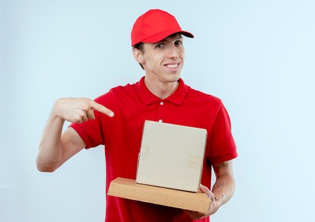 Jonge bezorger in rood uniform en pet met kartonnen dozen wijzend met wijsvinger naar hen glimlachend zelfverzekerd staande over witte muur Gratis Foto