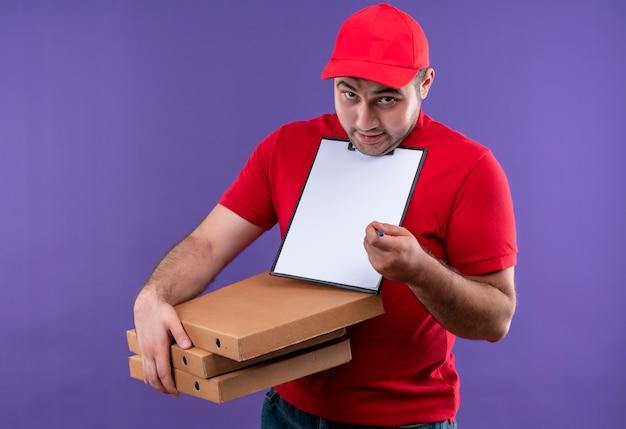 Jonge bezorger in rood uniform en pet met pizzadozen en klembord met blanco pagina's glimlachend verward vragen om handtekening staande over paarse muur Gratis Foto
