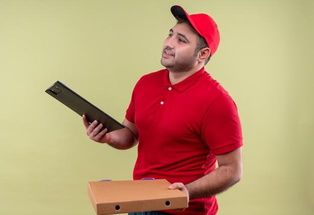 Jonge bezorger in rood uniform en pet met pizzadozen en klembord opzij kijken met glimlach op gezicht staande over groene muur Gratis Foto