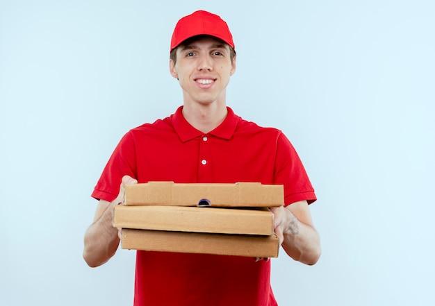 Jonge bezorger in rood uniform en pet met pizzadozen op zoek naar de voorkant met zelfverzekerde uitdrukking staande over witte muur Gratis Foto