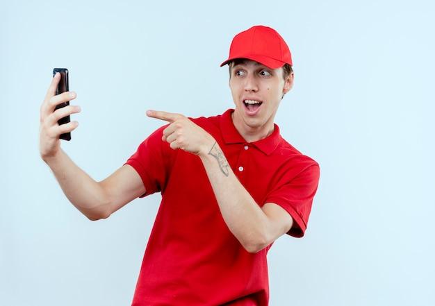 Jonge bezorger in rood uniform en pet met smartphone selfie glimlachend wijzend met vinger naar zijn smartphonecamera staande over witte muur Gratis Foto
