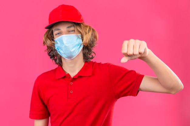 Jonge bezorger in rood uniform met medisch masker knipogen gebaren vuist hobbel alsof groet goedkeurend of als teken van respect over geïsoleerde roze achtergrond Gratis Foto