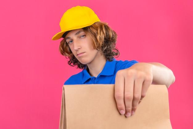 Jonge bezorger met blauw poloshirt en gele pet met papieren pakket in handen kijkend naar camera met scepticus en nerveus staande over geïsoleerde roze achtergrond Gratis Foto