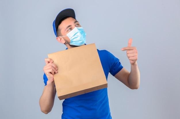 Jonge bezorger met blauw poloshirt en pet met beschermend medisch masker papier pakket met afhaalmaaltijden vasthoudend naar dit pakket met vinger glimlachend over geïsoleerde witte chtergro Gratis Foto