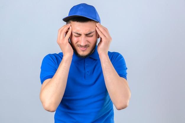 Jonge bezorger met blauw poloshirt en pet op zoek onwel aanraken van hoofd lijdt aan sterke hoofdpijn over geïsoleerde witte achtergrond Gratis Foto