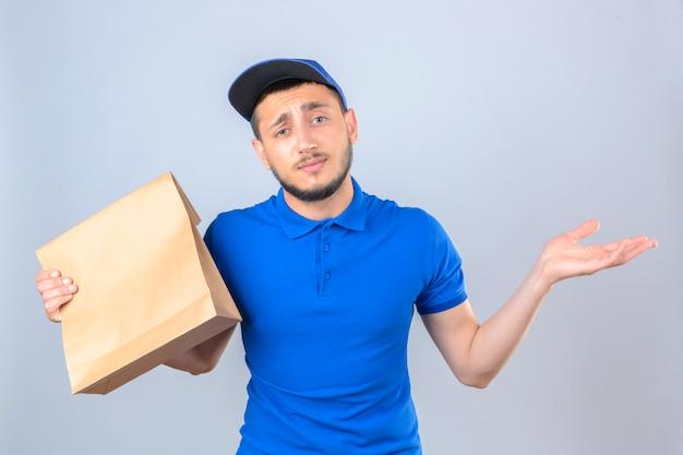 Jonge bezorger met blauwe polo shirt en pet staan met papieren pakket met afhaalmaaltijden verward met opgeheven handen over geïsoleerde witte achtergrond Gratis Foto
