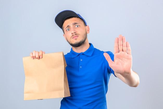 Jonge bezorger met blauwe poloshirt en pet met papieren zak met afhaalmaaltijden op zoek bezorgd stop gebaar maken met hand over geïsoleerde witte achtergrond Gratis Foto
