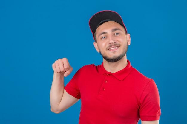 Jonge bezorger met rood poloshirt en pet kijkt naar camera glimlachend vriendelijk gebaren vuist hobbel alsof begroeting goedkeurend of als teken van respect over geïsoleerde blauwe achtergrond Gratis Foto