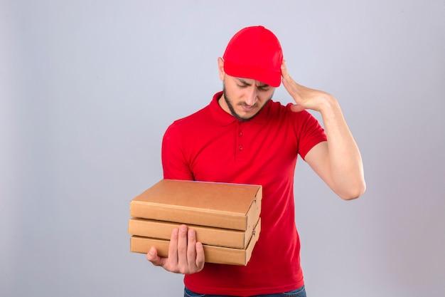 Jonge bezorger met rood poloshirt en pet staan met stapel pizzadozen op zoek overwerkt aanraken van hoofd lijden aan hoofdpijn over geïsoleerde witte achtergrond Gratis Foto