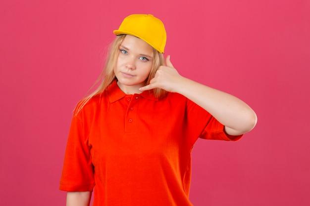 Jonge bezorgvrouw die een rood poloshirt en een gele pet draagt en bel me gebaar maakt op zoek naar zelfverzekerd over geïsoleerde roze achtergrond Gratis Foto