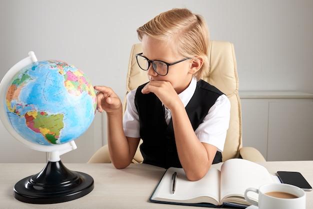Jonge blanke jongen zittend in executive stoel in office en kijken naar earth globe Gratis Foto