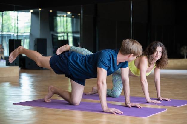 Jonge blanke man en vrouw in yoga klas training op de kamer Premium Foto