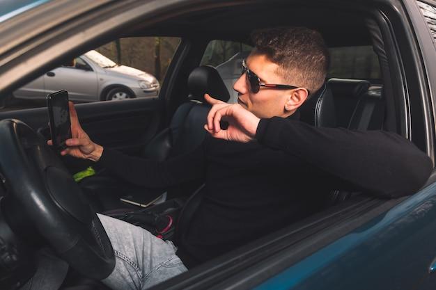 Jonge blanke man in een auto met behulp van een smartphone Premium Foto