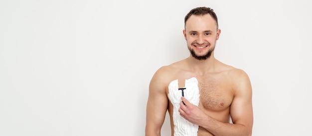 Jonge blanke man met baard houdt scheermes zijn borst met wit scheerschuim op witte muur Premium Foto