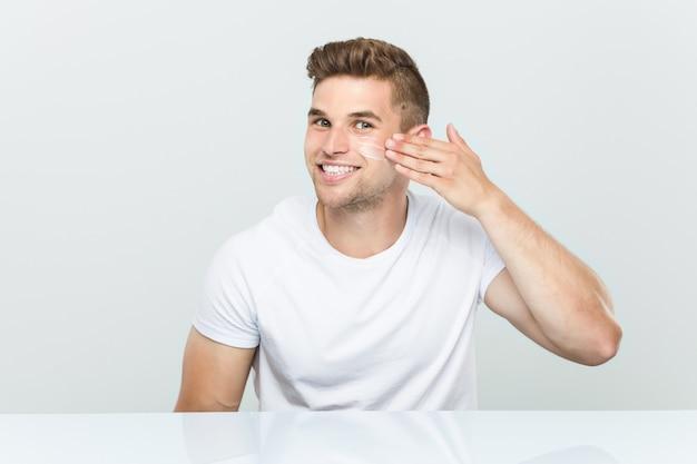 Jonge blanke man met behulp van gezichtscrème Premium Foto