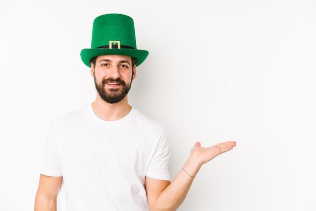 Jonge blanke man met een heilige patricks hoed geïsoleerd met een kopie ruimte op een palm en met een andere hand op de taille. Premium Foto