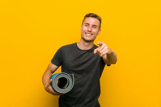 Jonge blanke man met een mat vrolijke glimlach wijzend naar de voorkant. Premium Foto